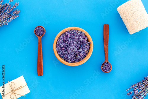Spa set with lavender spa salt. Purple spa salt near dry lavender branches and washcloth on blue background top view pattern