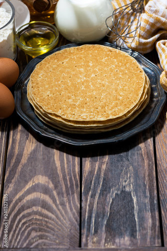 traditional thin pancakes and ingredients, vertical
