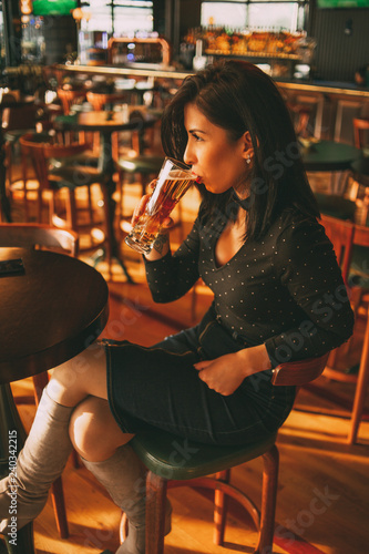 Beautiful Brunette Woman Drinking Beer in the Pub