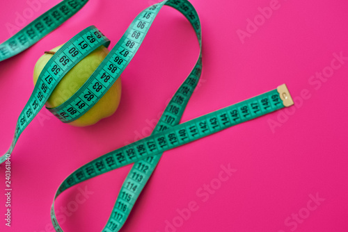 Green apple measured the meter on a pink background - 240361840