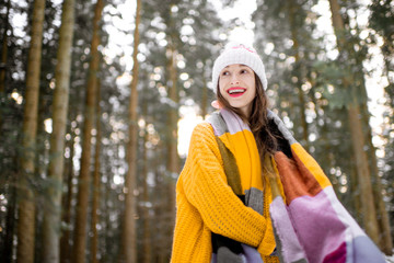 Portrait of a young playful woman dressed in bright winter clothes standing in pine forest enjoying winter time © rh2010