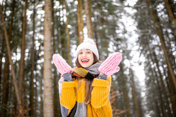 Portrait of a young woman dressed in bright winter clothes standing in pine forest during the winter time