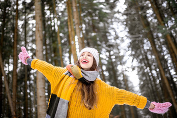 Portrait of a young playful woman dressed in bright winter clothes enjoying nature in the pine forest during the winter © rh2010