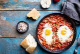 Shakshuka, Fried Eggs in Tomato Sauce in iron frying pan. Typical Israel food. Top view. - 240377095