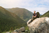 A tourist on a high mountain looks at nature. A man with a backpack sits on a large stone and looks at the landscape. - 240377215