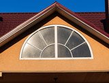Arched window with white frame, close up, house exterior