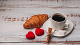 Cup of coffee and a croissant for Valentine's day