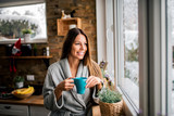 Smiling young woman in bathrobe drinking coffee in the morning, looking through window. - 240395614
