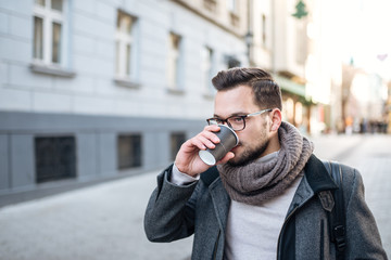 Close-up image of young man walking and drinking coffee in the city street.