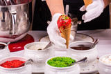 The strawberry ice cream which is flowing down from ice cream cone with grated nuts and grated chocolate