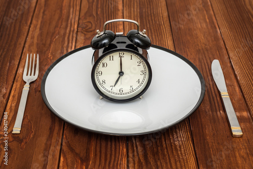Alarm clock on plate with knife and fork on wooden background. Weight loss or diet concept - 240417484