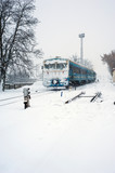 Train on the railway in heavy snow storm. Passenger train moves on the railway in winter in Ukraine.