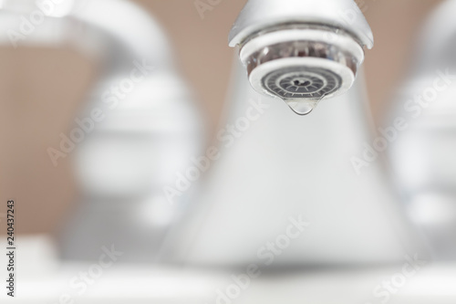 Bathroom faucet with dripping water close-up