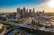 Quadro Drone view of downtown Los Angeles or LA skyline with skyscrapers and freeway traffic below.