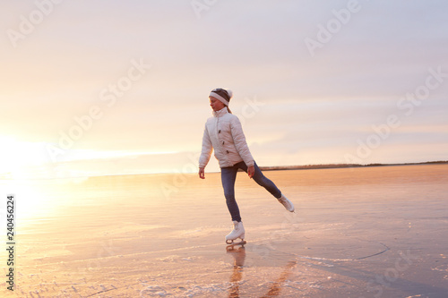 Cute little girl is skating on a frozen lake. Silhouette. Happy child playing on a winter walk in nature. - 240456224