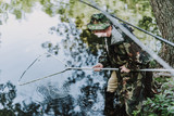 Aged professional concentrated angler using fishing equipment - 240468003