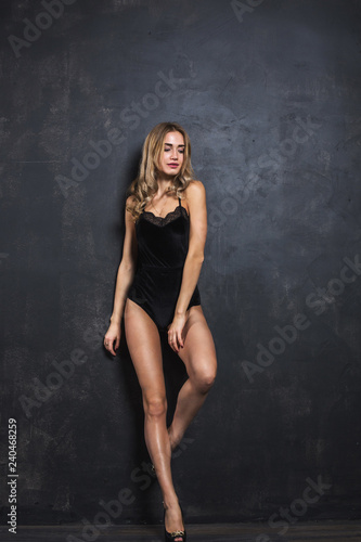 mata magnetyczna Beautiful and attractive girl with loose wavy hair and slim figure is posing in the black body, dark background