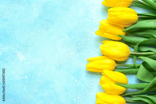 Leinwanddruck Bild Celebrate background with bouquet of yellow tulips.Top view with copy space.