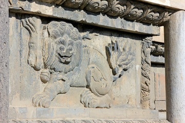 lion sculptures in grey wall