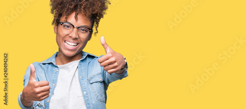 Leinwanddruck Bild Beautiful young african american woman wearing glasses over isolated background approving doing positive gesture with hand, thumbs up smiling and happy for success. Looking at the camera