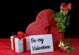 Beautiful image in shades of red for Valentine's Day in February. Silk roses in brass vase with gift and blank card on velvety table cloth. Greeting card added.  Black background.