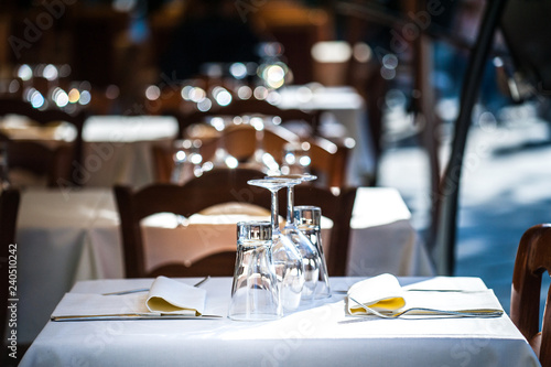 Served table in a street caffe with white tablecloth, glasses, and napkins. Selective focus.