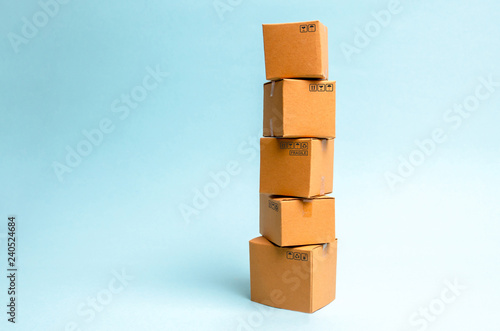 Tower of cardboard boxes on a blue background. The concept of moving and delivery of goods and goods. Commerce and business processes, logistics, distribution and sales.