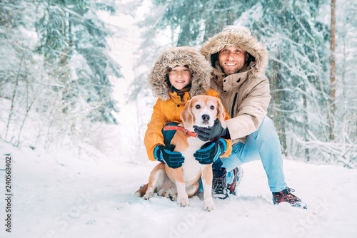 Leinwanddruck Bild Father and son  dressed in Warm Hooded Casual Parka Jacket Outerwear walking with their beagle dog in snowy forest cheerful smiling faces portrait. Pets in family and winter outfit concept image.