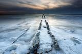 old wooden breakwater on frozen lake