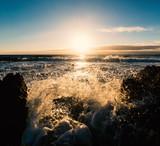 Splash against the rocks at sunset