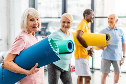 selective focus of senior sportswoman holding fitness mat and her friends standing behind at gym - 240621664