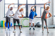 Leinwanddruck Bild - happy multiethnic senior sportspeople synchronous exercising at sports hall