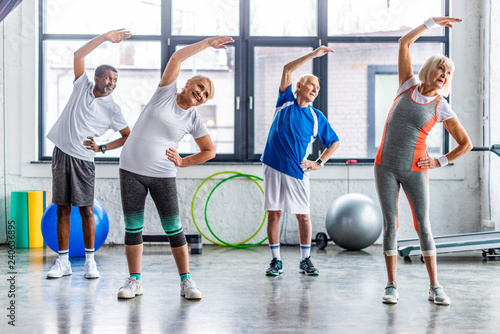 Leinwanddruck Bild happy multiethnic senior sportspeople synchronous exercising at sports hall