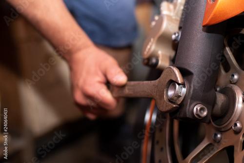 Mechaniker repariert sein Motorrad mit einem Schraubenschlüssel