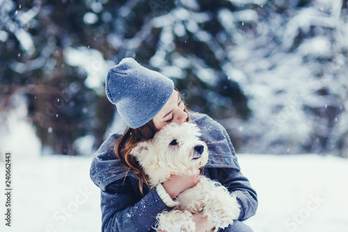 Young dog owner girl plays with white terrier in park outdoor.