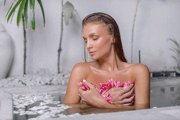 Beautiful girl in a tropical bathroom with flower petals. SPA  © fotoplaton