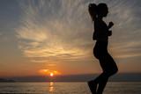 young woman does exercise at sunrise © lymdigital