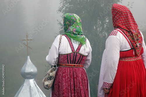 Two women in traditional Slavic costumes, standing on a hill, looking at the dome of the Church . © andreysha74