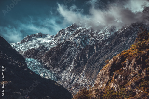 Foto Murales Glacier and clouds over rugged mountains