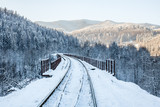railway in snow on the railway bridge in the mountains © AlexR