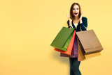 Beautiful woman with shopping bags, over yellow - 240734044