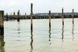 Coastal harbor with wooden pier dock on sandy rocky beach