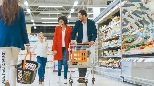 Leinwandbild Motiv At the Supermarket: Happy Family of Three, Holding Hands, Walks Through Fresh Produce Section of the Store. Father, Mother and Daughter Having Fun Time Shopping.