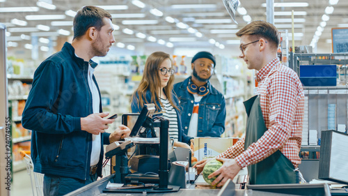 Leinwanddruck Bild At the Supermarket: Checkout Counter Customer Pays with Smartphone for His Items. Big Shopping Mall with Friendly Cashier, Small Lines and Modern Wireless Paying Terminal System.