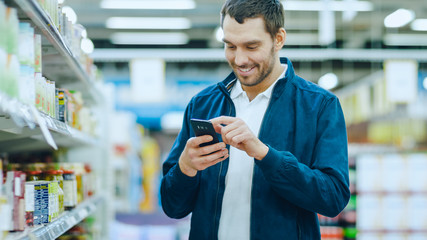 At the Supermarket: Handsome Man Uses Smartphone, Smiles while Standing at the Canned Goods Section.