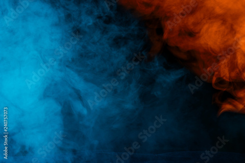blue-orange abstraction thick and transparent cigarette vapor on a dark background - 240757073