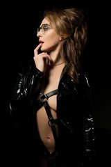 Sexy brunette in black leather jacket in the dark