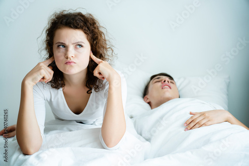 Leinwandbild Motiv Caucasian Couple on bed with white mattress Man snoring loud makes women feel annoyed. Causes Obstructive Sleep Apnea Stroke Chronic depression Sexual dysfunction It can be  cause of divorce spouse.