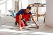 Leinwanddruck Bild - Master is wearing work clothes, is checking horizon of installing tiles, using building level, adjusting, professional repairing work