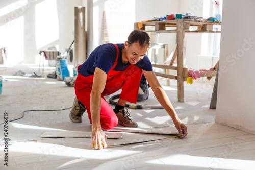 Leinwanddruck Bild Master is wearing work clothes, is checking horizon of installing tiles, using building level, adjusting, professional repairing work